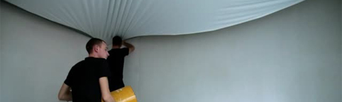 A construction contractor installs a stretch ceiling in a apartment.